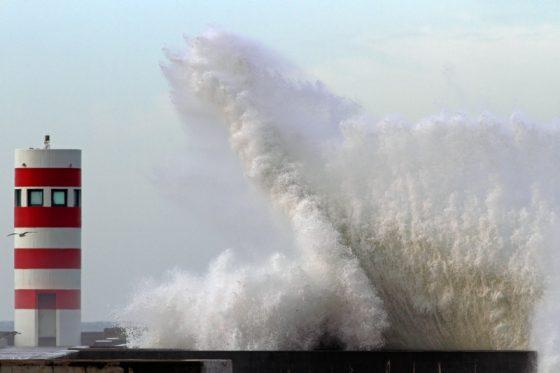 hoge golven in Portugal bij vuurtoren